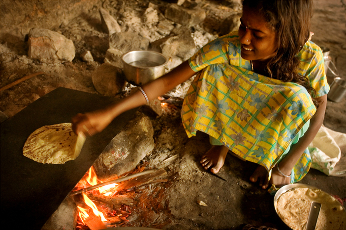 young girl cooking chapatti