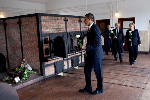 President Barack Obama places a flower at a memorial at Buchenwald Nazi concentration camp, June 5, 2009. With the President are German chancellor Angela Merkel, Holocaust survivor Elie Wiesel, and camp survivor Bertrand Herz.