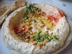 A dish of hummus (A Lebanese Dish) with pine n...