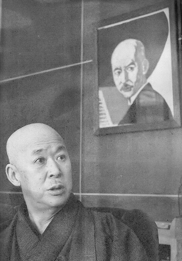 1952年の山田耕筰。後ろの絵は恩地孝四郎による山田の肖像 Wikipediaより