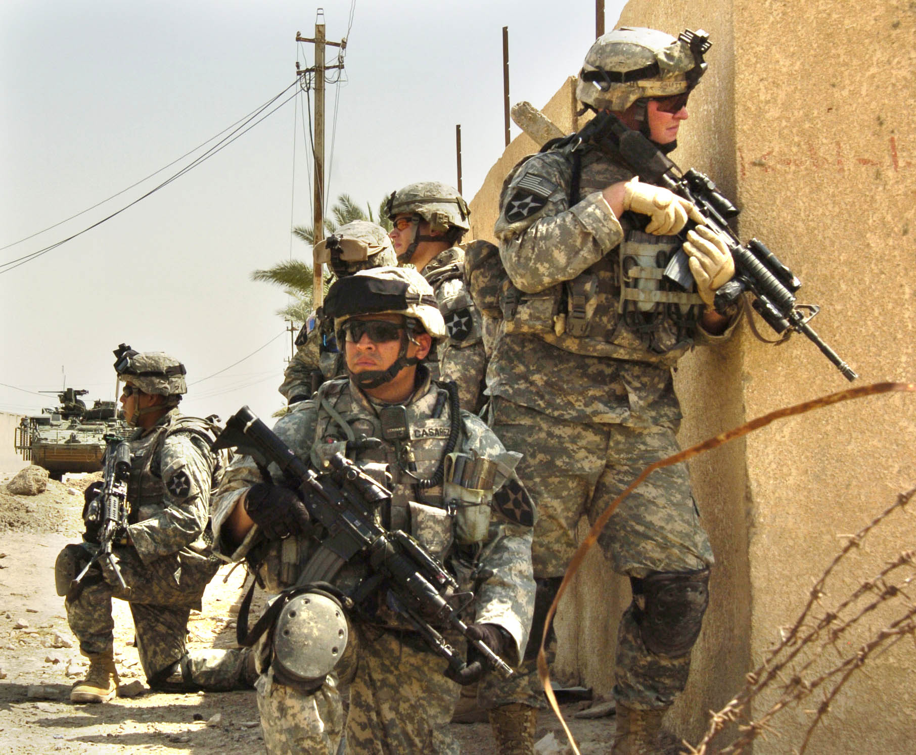 U.S. Army soldiers from the 2nd Infantry Division, patrol the streets of Baghdad, Iraq during the Iraq War in August 2006, while wearing the Army Combat Uniform and Interceptor body armor.