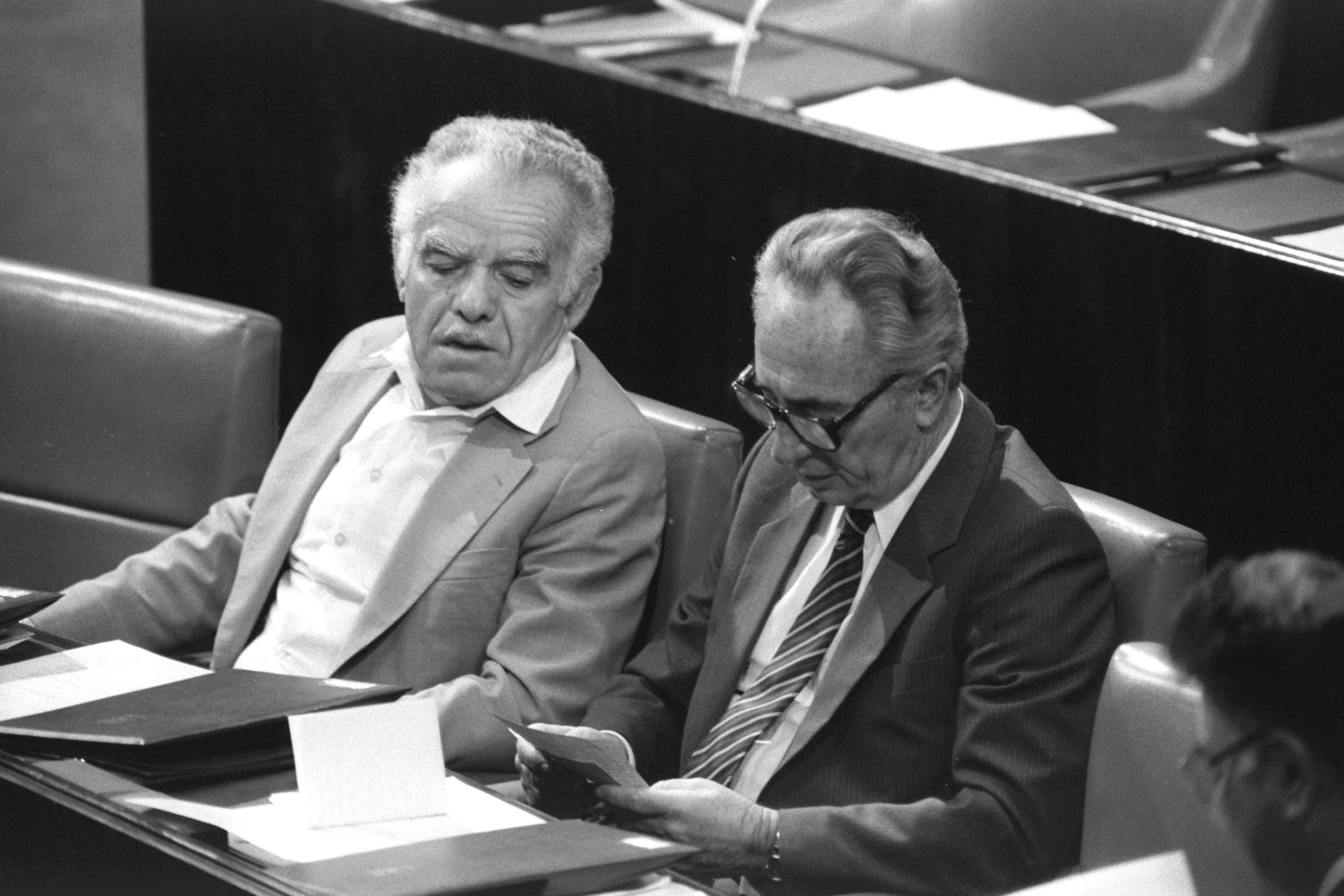 ראש הממשלה שמעון פרס וסגנו יצחק שמיר ליד שולחן הממשלה בכנסת, נובמבר 1985. באוקטובר 1986 התחלפו ביניהם האישים בתפקידיהם.