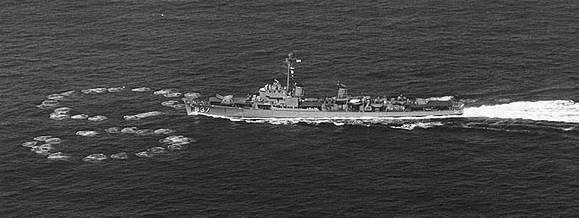 A destroyer moving to the left; on the water just ahead of her are two rings of small circular waves, one to either side of her path. The rings nearly meet directly ahead of her and are each about half her length in diameter.