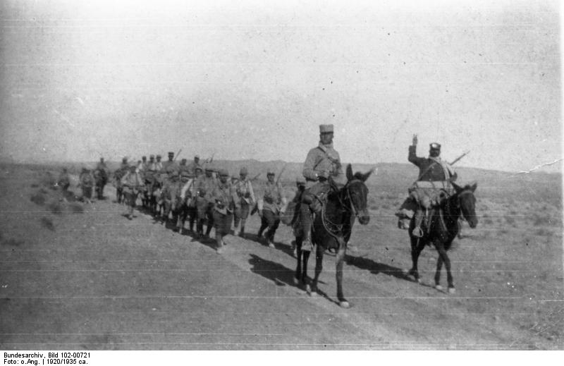 A column of around a dozen Foreign Legion troops on foot, followed by a similar number mounted on donkeys and led by two mounted officers/NCOs proceeding along a road