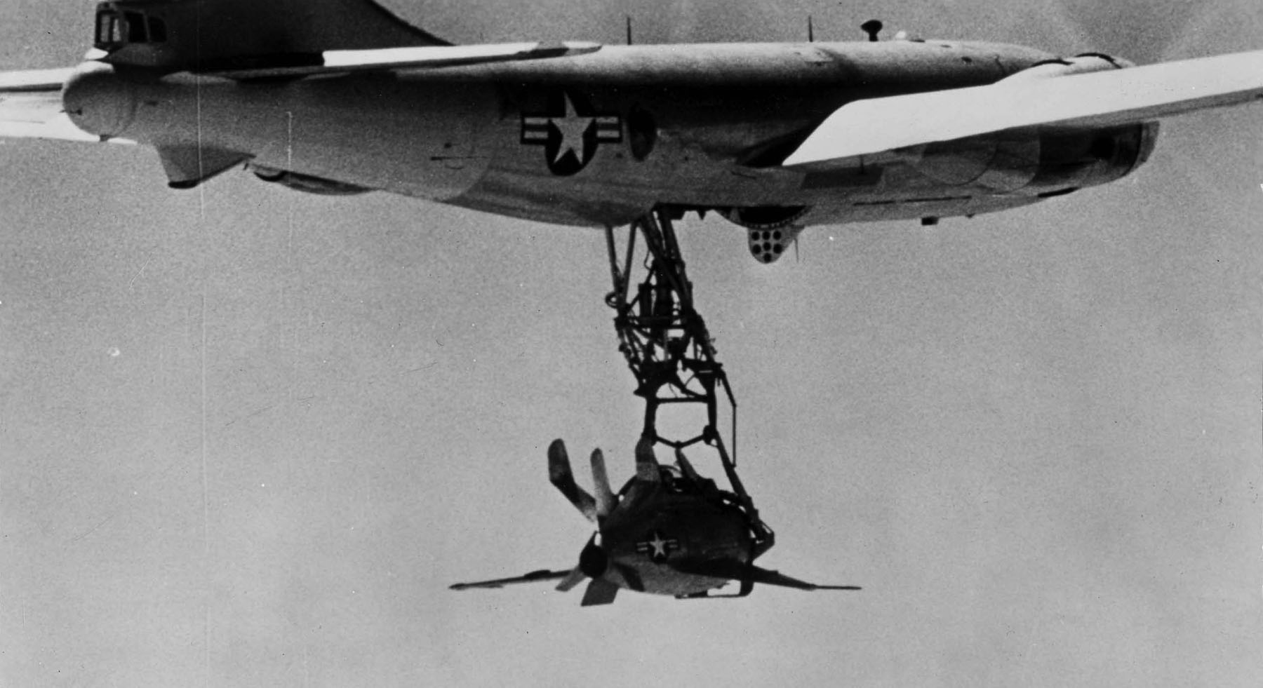 Black-and-white photograph shows diminutive jet fighter suspended from a large aircraft in flight, through a trapeze.