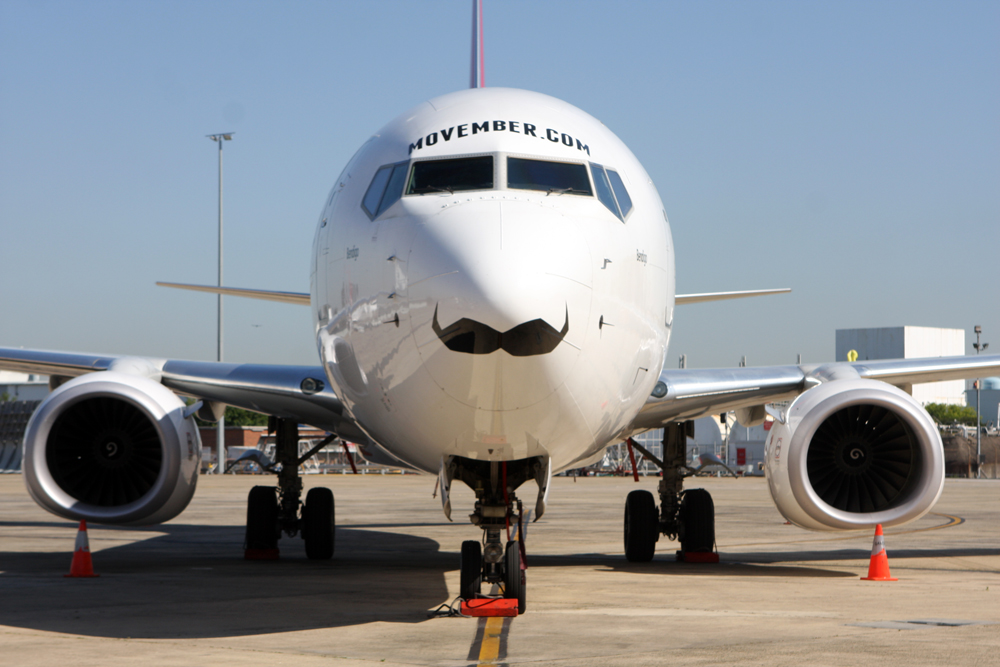 Photo of a commercial airplane with a moustache under its nose, with Movember.com printed above cockpit windows
