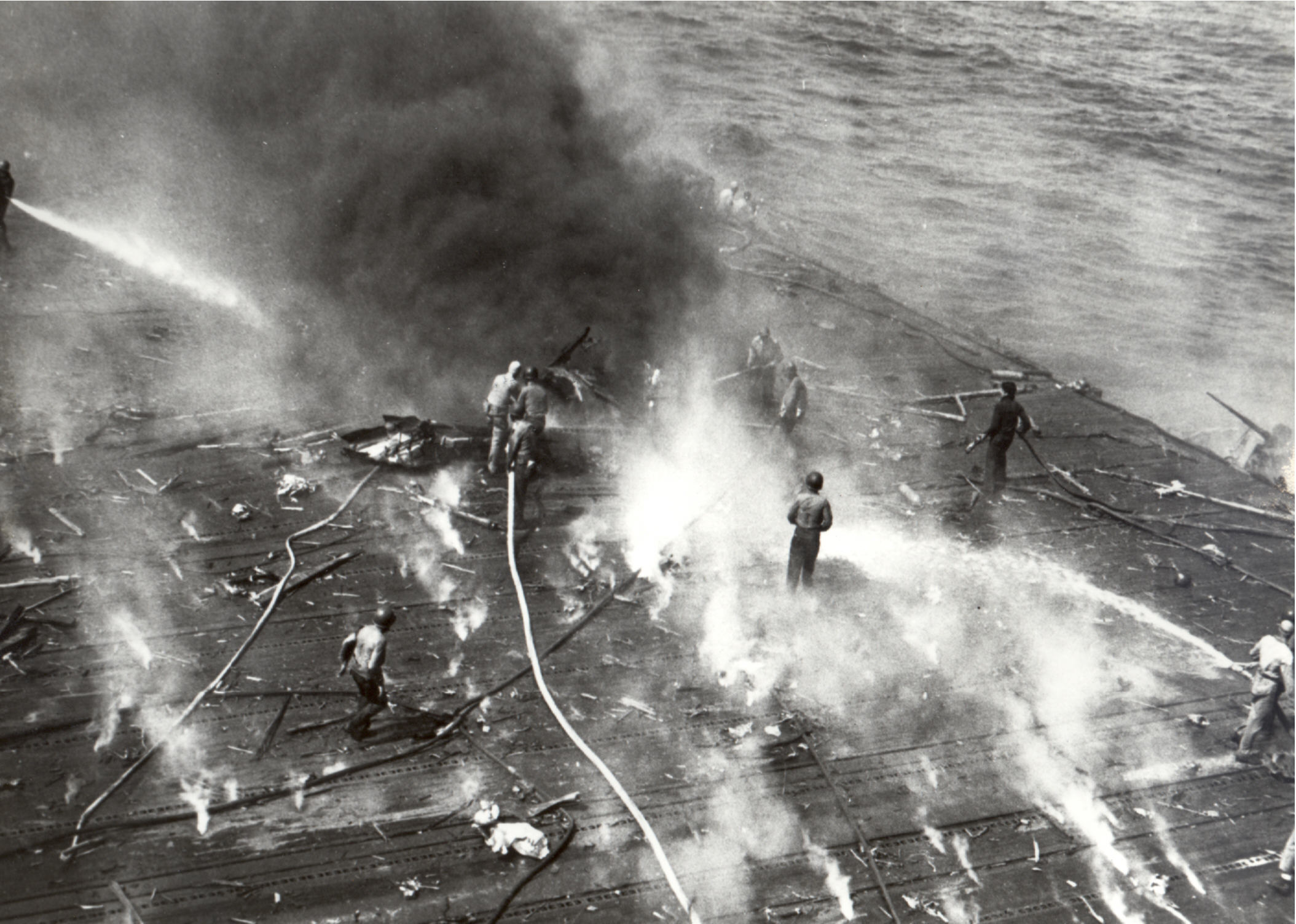Midway. Note the sailor in the foreground attempting to repair the wooden flight deck. The forward arresting wires can also be seen in the foreground. Date