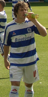 A footballer wearing a white and blue hooped football shirt and shorts. He is standing on the pitch and drinking from a bottle.