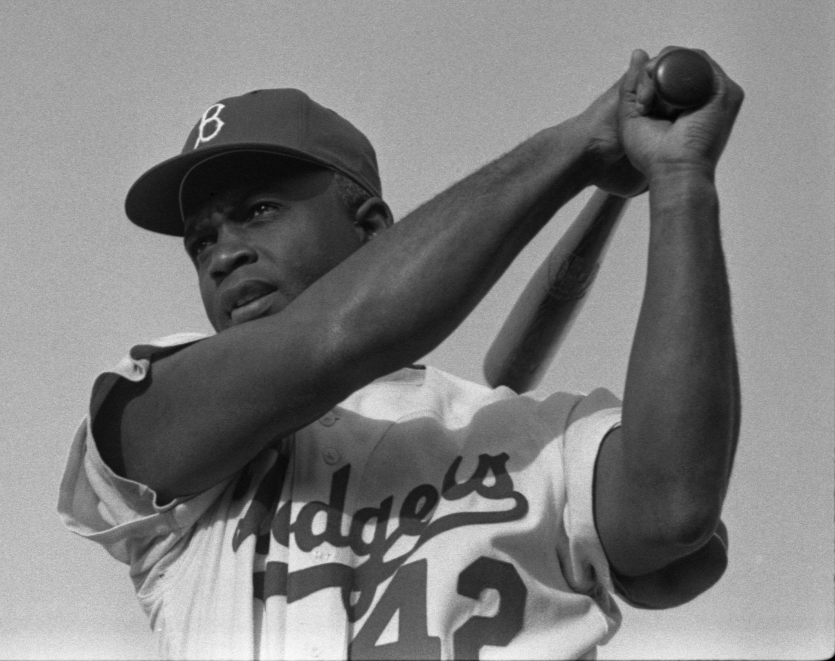 Jackie Robinson swinging a bat in Dodgers uniform, 1954. Photo by Bob Sandberg. Published in LOOK, v. 19, no. 4, 1955 Feb. 22, p. 78.