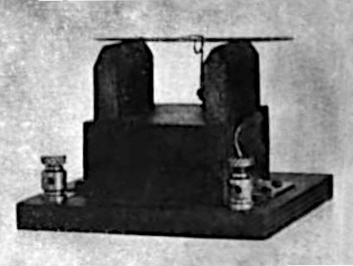 """Microphone"" coherer detector from 1909 similar to one Pickard discovered rectification with, widely used in the first receivers. It consists of a steel needle resting on two carbon blocks. A semiconducting corrosion layer on the steel may have been responsible for the rectification. Microphone wireless detector 1909.png"