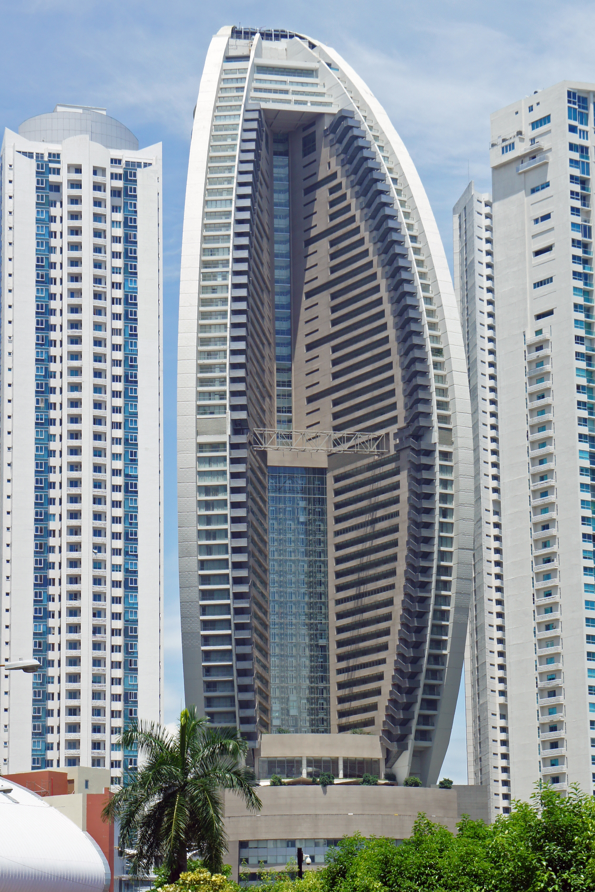 A Tall White And Grey Colored Building With Curved Facade Towering The Trump Ocean Club International Hotel