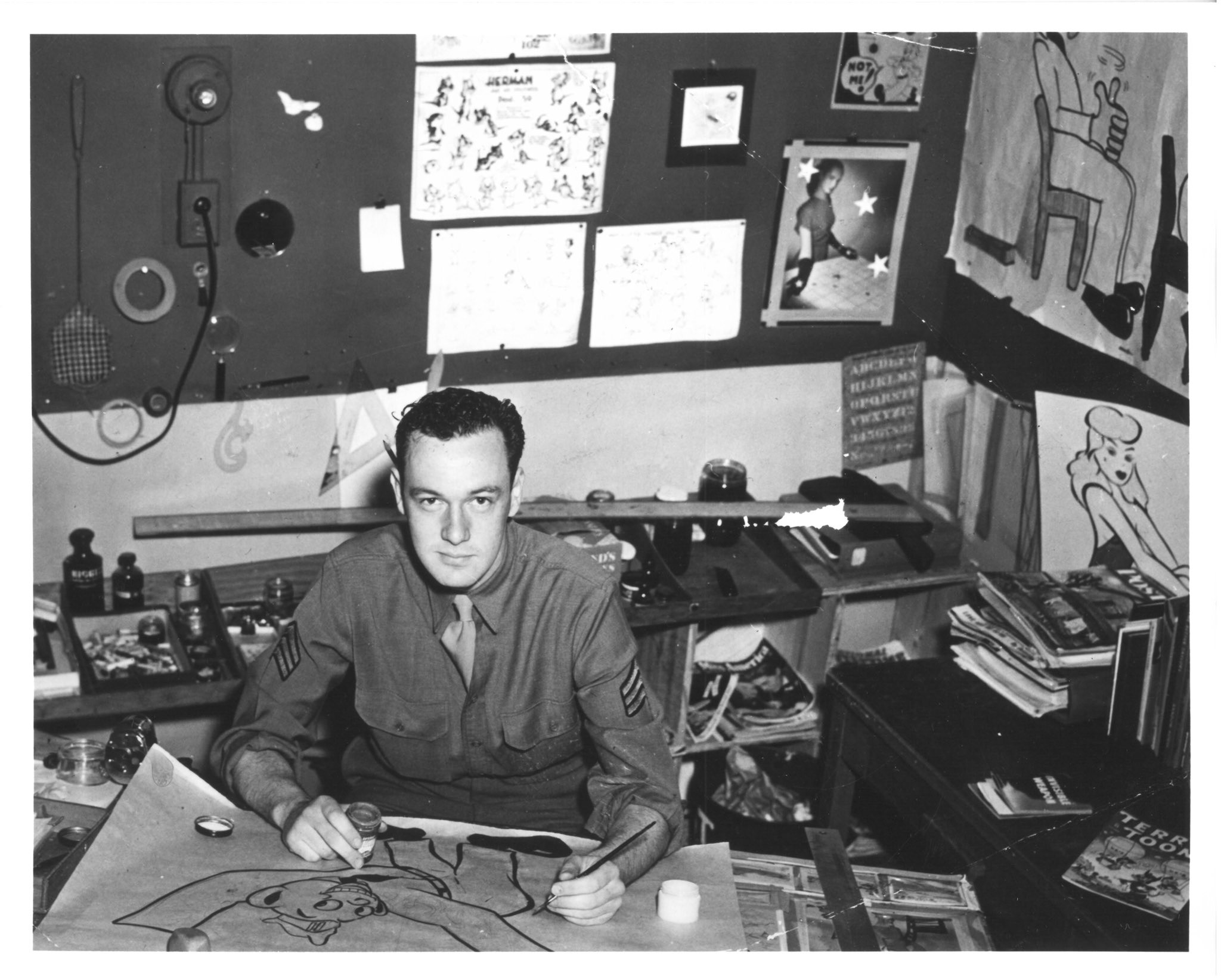 Stan Lee sits in a office, with several drawings on the background. He is sitting down in front of a table; on that table he is drawing an image.
