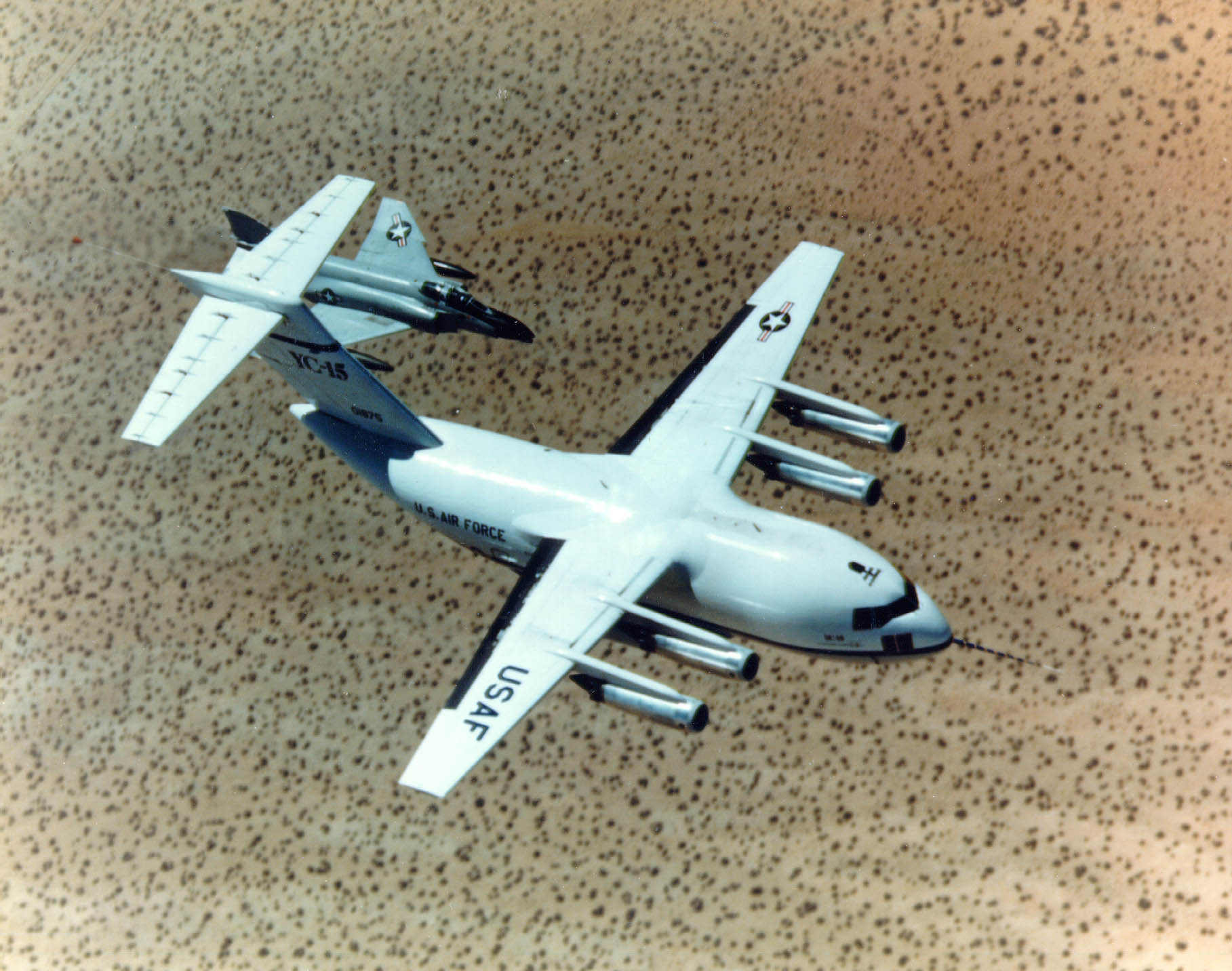 Top view of cargo aircraft in-flight, trailed by a fighter chase aircraft. Under each un-swept wing are two engines suspended forward ahead the leading edge.