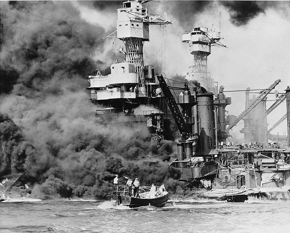 Pearl Harbor, Hawaii. A small boat rescues a seaman from the 31,800 ton USS West Virginia burning in the foreground.