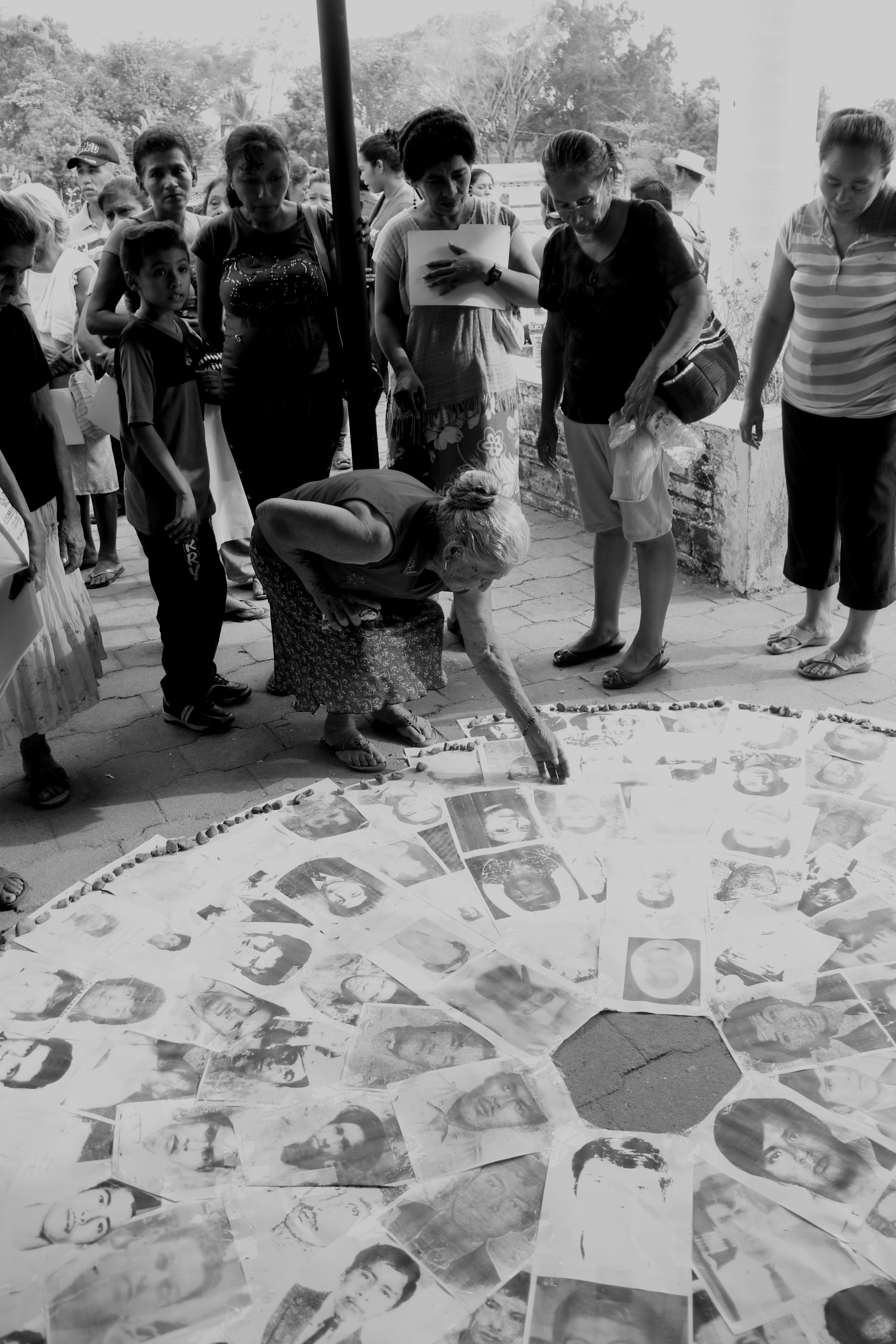 Black and white photgraph of a memorial in Mexico, with an elderly woman adding a picture