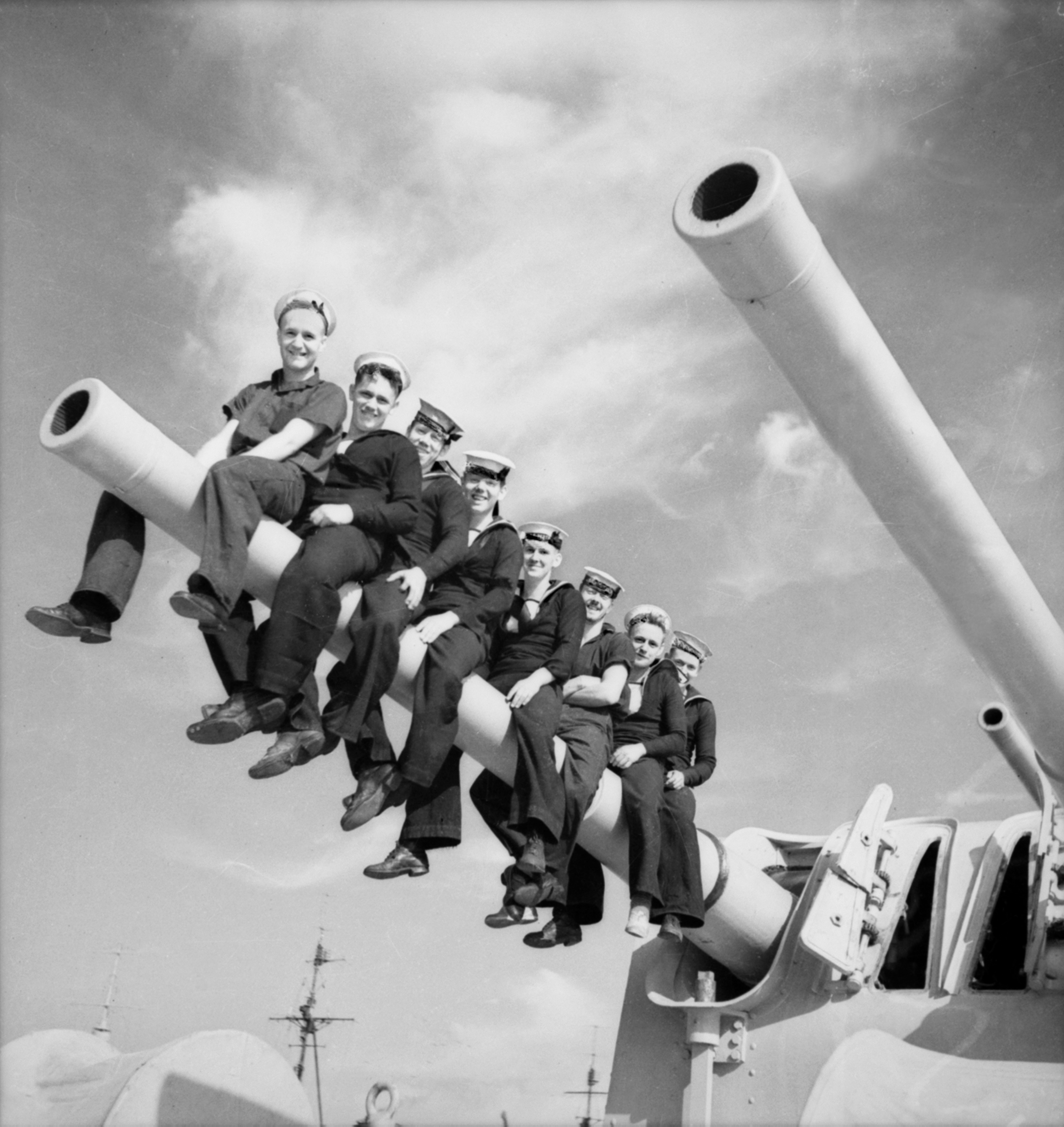 HMAS_Perth_-_men_astride_gun_turret,_194