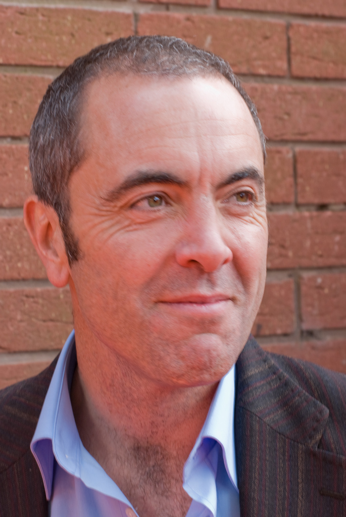 A man with a receding hairline smiles. He wears a light blue shirt with an open collar and a charcoal grey jacket.