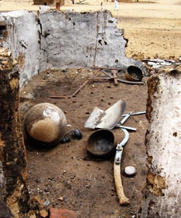 Burnt hut in Darfur closeup of tools
