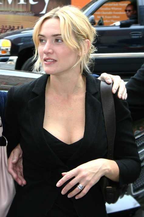 a young woman, with casually styled blonde hair wears a black jacket over a black dress. She is walking along a street; behind her a man sits in a car looking in her direction.