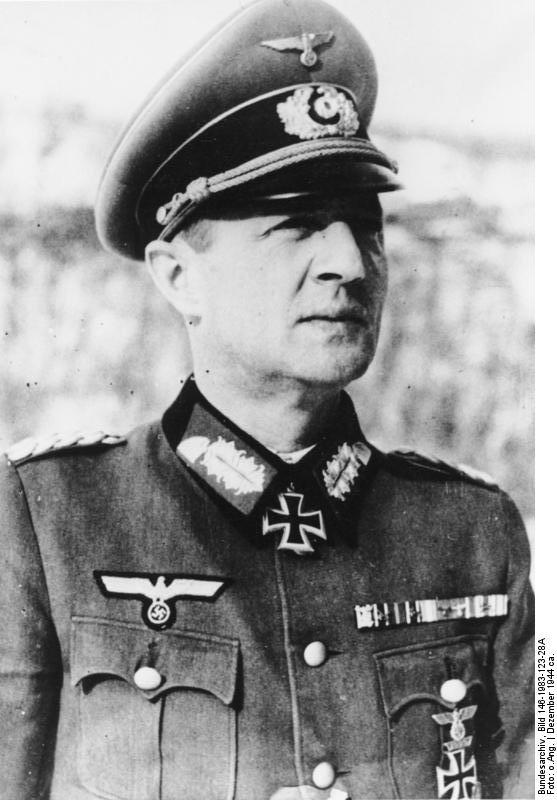 alt=A man wearing a military uniform, peaked cap and neck order in the shape of a cross.