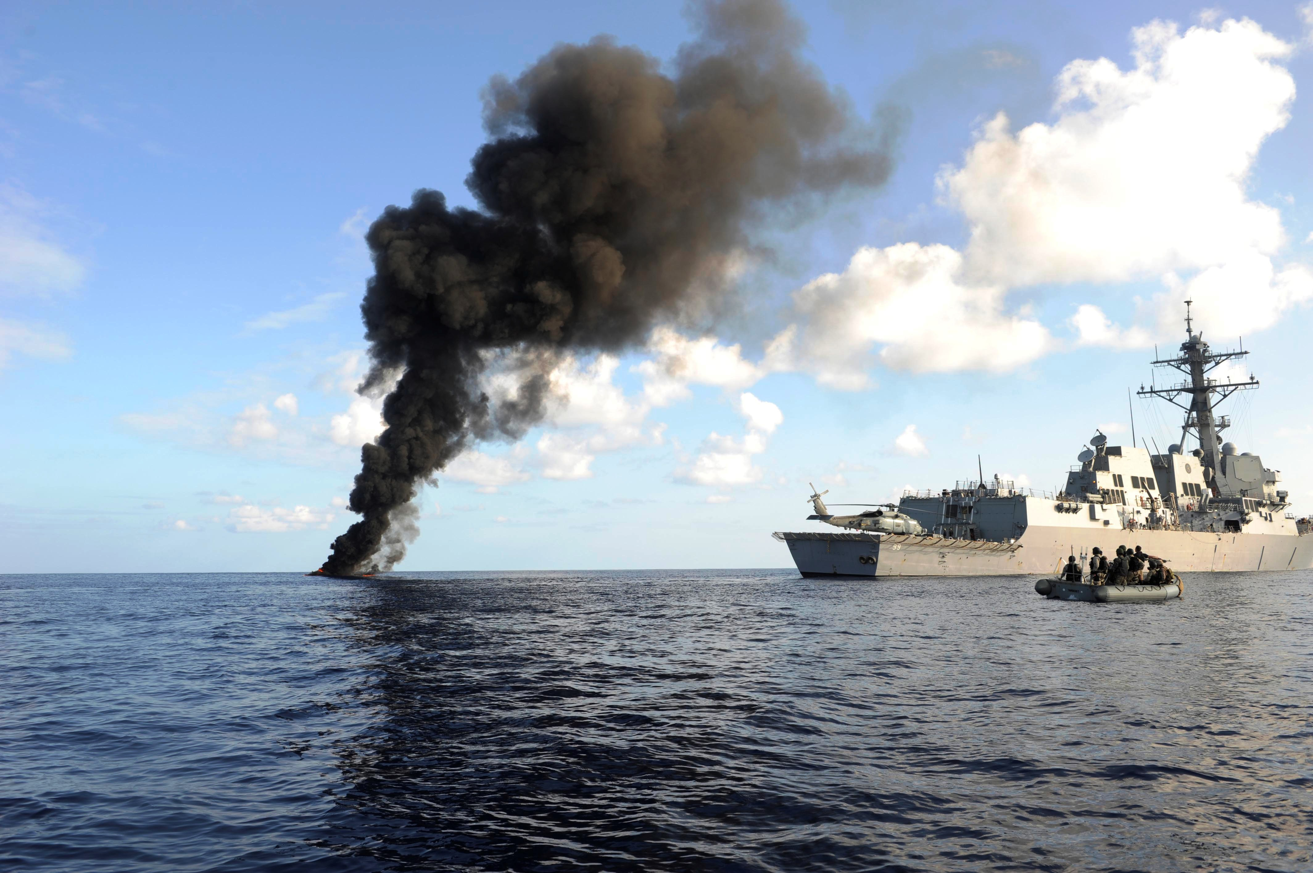 A tall plume of black smoke rises from the blue ocean waters next to a large gray battleship and a small black inflatable boat.
