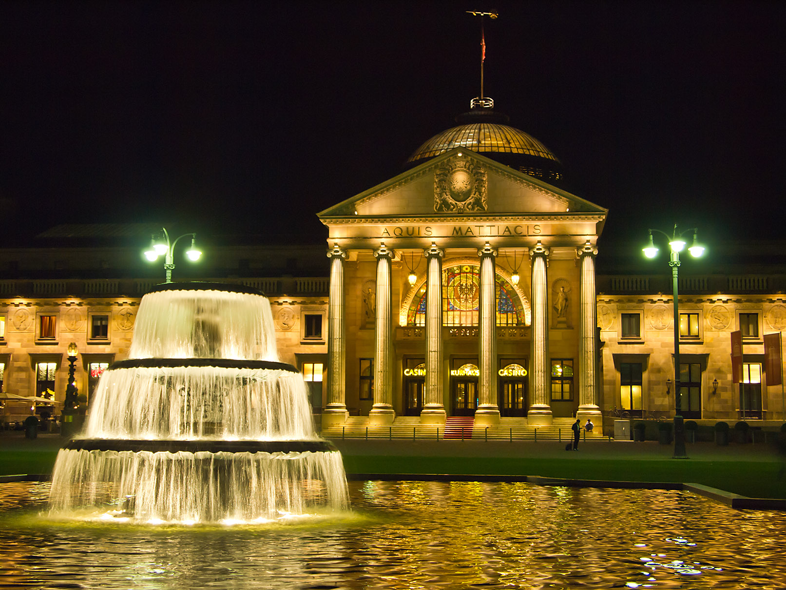 Kurhaus Wiesbaden (spa house) with one Fountain of the Bowling Green in the evening, German