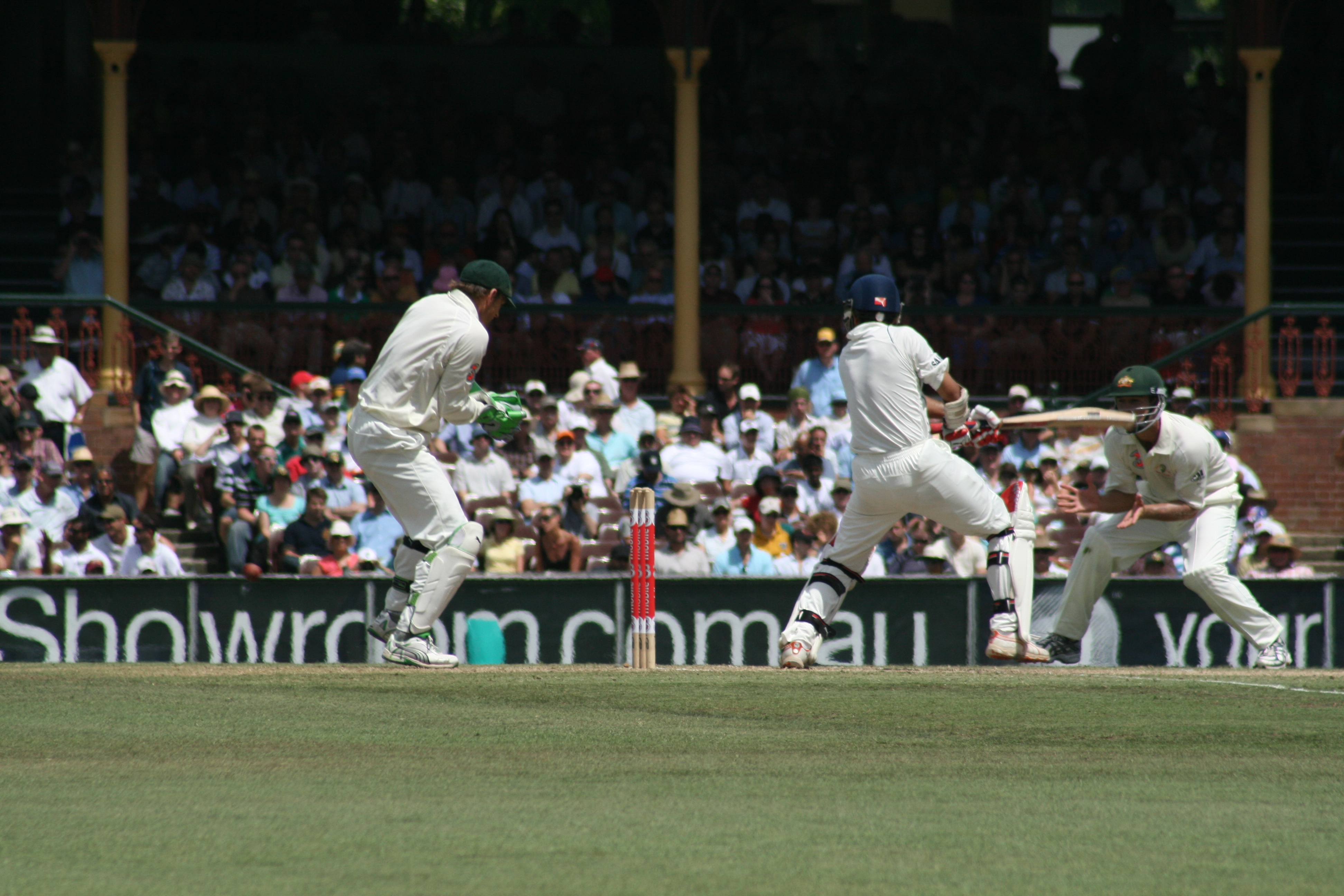A cricket match being held. The batsman hits the ball and the other players try to catch it. The green field and the audience are visible in the far.