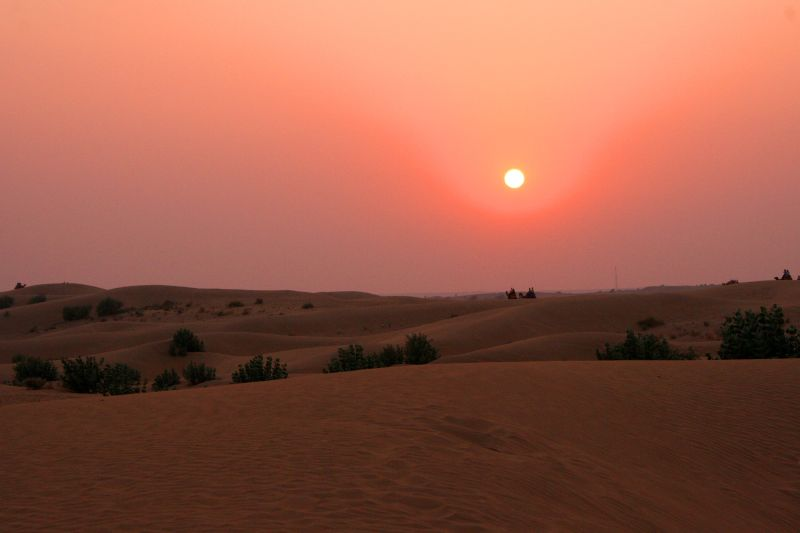View of dunes at sunset. The setting sun hangs low and dim in a sky graded from fiery orange at top to maroon near the horizon. Terrestrial features are difficult to discern in the crepuscular illumination.