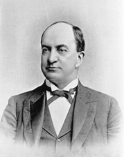 A balding man with dark hair wearing a black jacket and tie and white shirt.