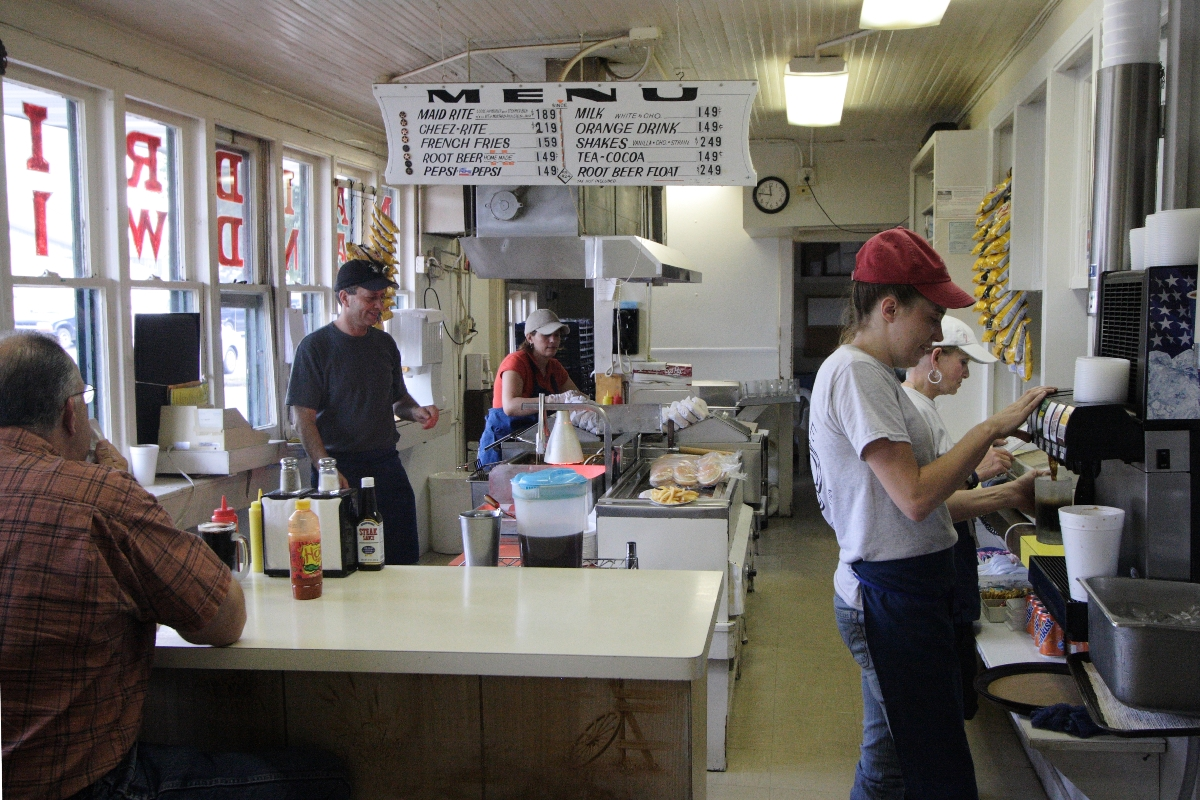 Inside a sandwich shop with people working and eating