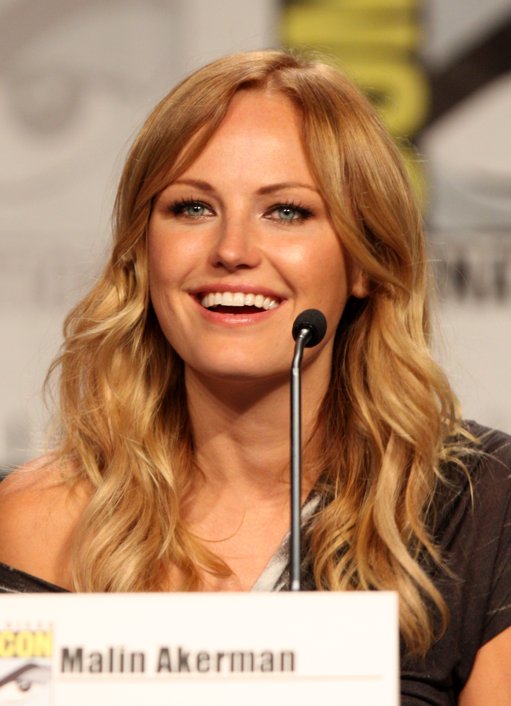 A woman (Malin Åkerman) with golden blonde hair and tan skin wears a brown shirt and smiles while sitting in front of a microphone. In front of her is also a name tag with 'Malin Akerman' written on it.