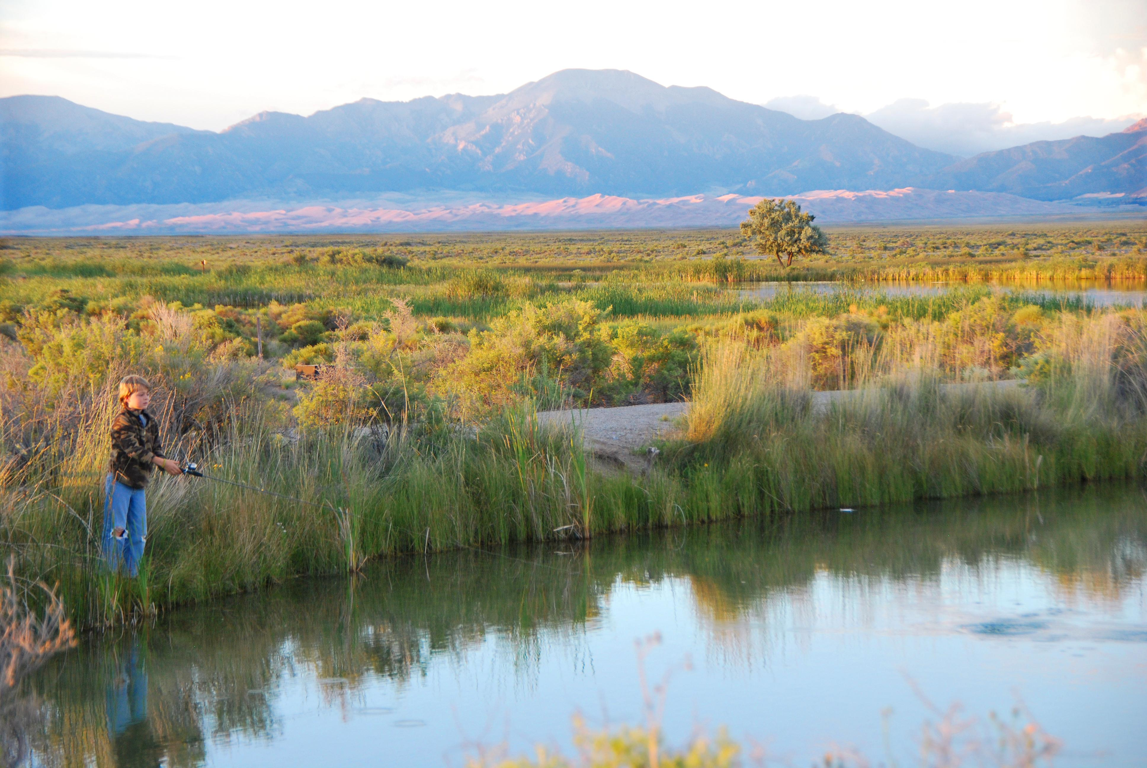 File Boy Fishing At Blanca Wetlands Dunes And Sangre De Cristo Mountains In Background
