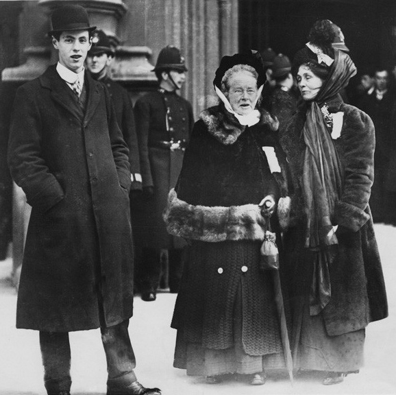 black and white photo of man standing with two women with policemen behind them