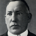 A black-and-white picture of a man with a moustache.