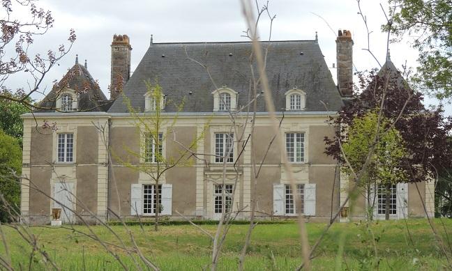 Château de Souvigné, corps de batiment principal et deux pavillons latéraux sur 1 étage plus les lanternes des combles sur toits plats avec 2 cheminée latérales sur batiment principal. Herbe au premier plan et branches d'arbres notamment devant le pavillon droit