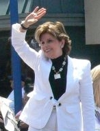A smiling woman in a white blazer raising her hand to either wave or block the sun