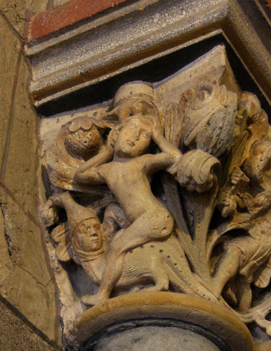 la foto di un capitello raffigurante una giovan donna che regge la parte sovrastante della colonna