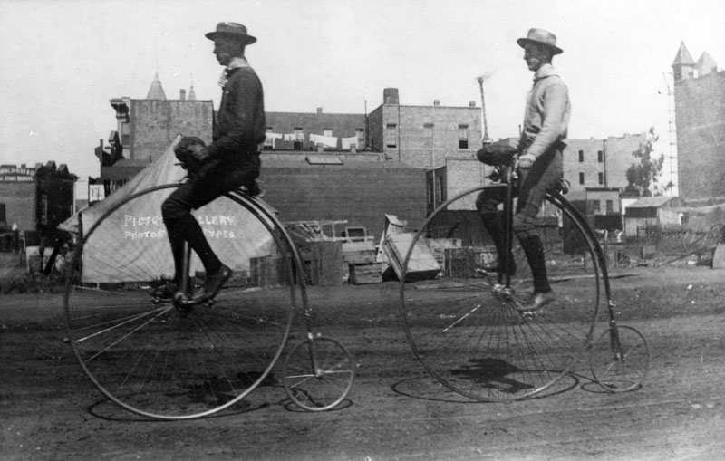 Vintage bike penny-farthing mounted by men