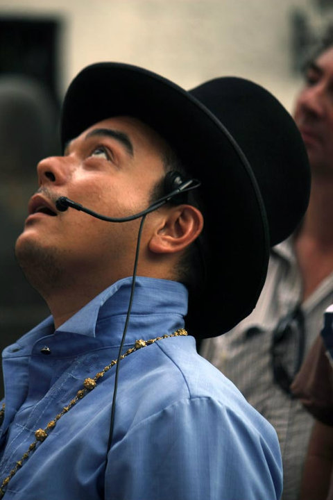 A head shot of Carlos Celdran wearing a top hat, headset microphone, and blue barong, looking skywards as he speaks.