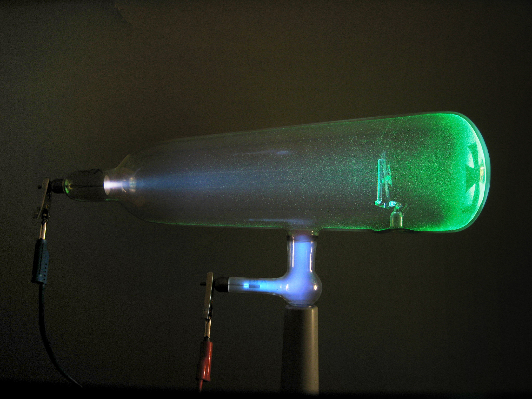 A glass tube containing a glowing green electron beam