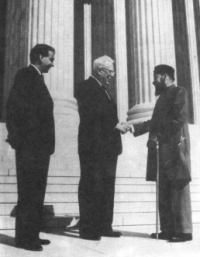 Earl Warren and Maulvi Tamizuddin Khan shake hands as a third man looks on