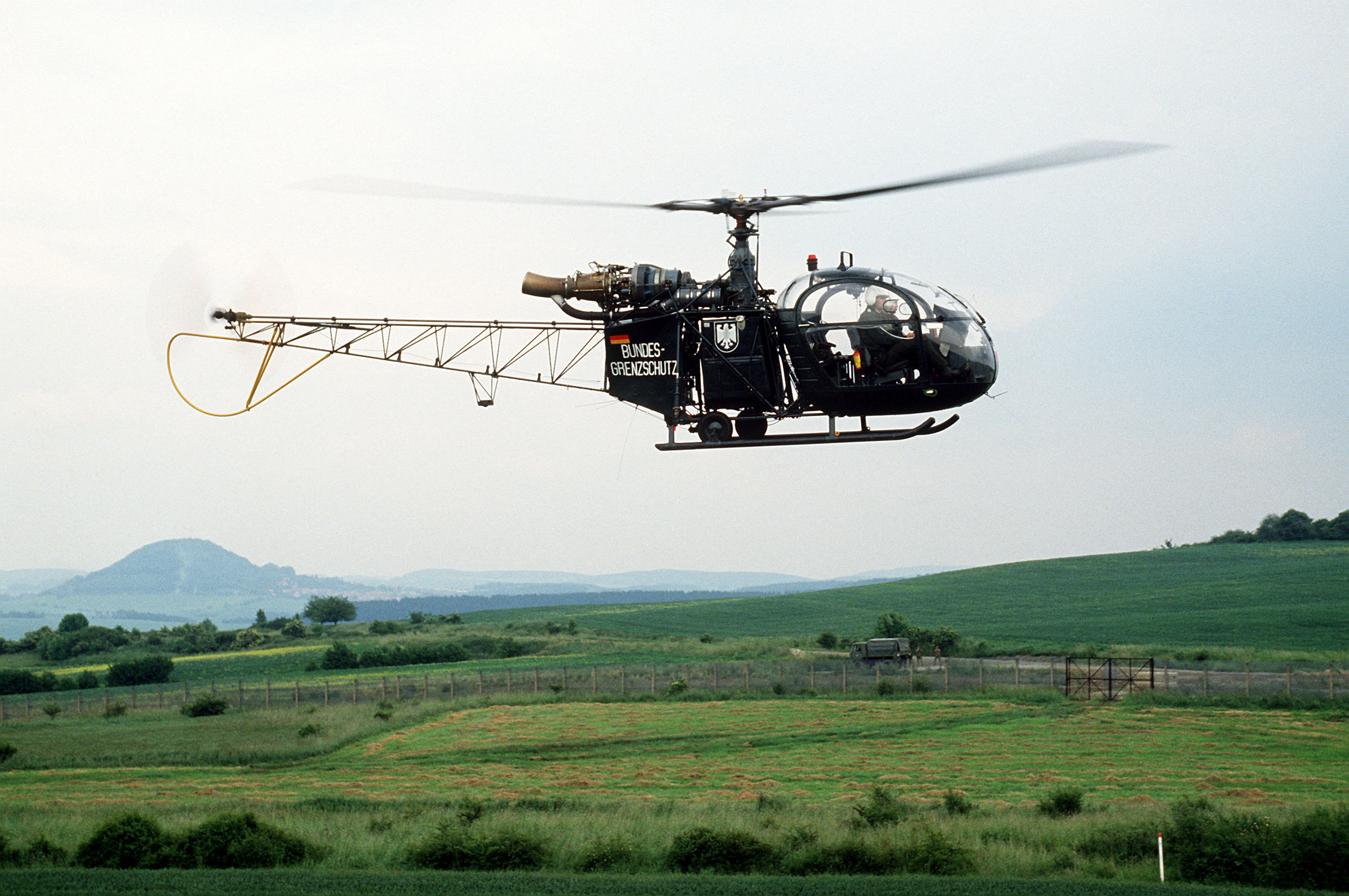 """Green-painted helicopter with """"Bundesgrenzschutz"""" on the side flies parallel to a border fence with a gate in it, behind which are two East German soldiers and a canvas-sided truck."""