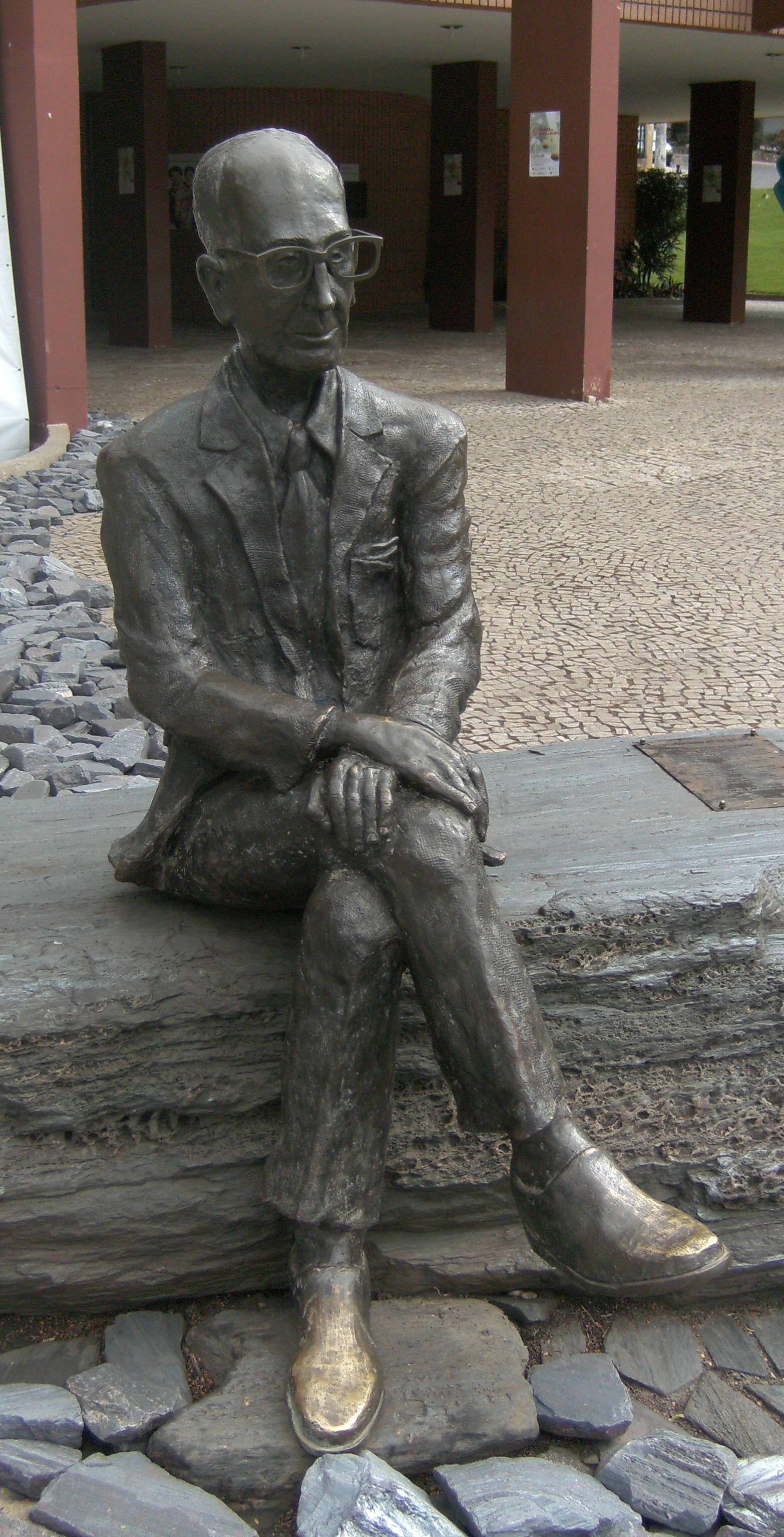 """Estátua de Drummond em Itabira. """"Outros leram da vida um capítulo, tu leste o livro inteiro"""""""