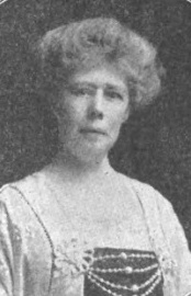 A middle-aged white woman with grey hair in a bouffant updo. She is wearing a dress with a square neckline and beaded embellishments across the bust.