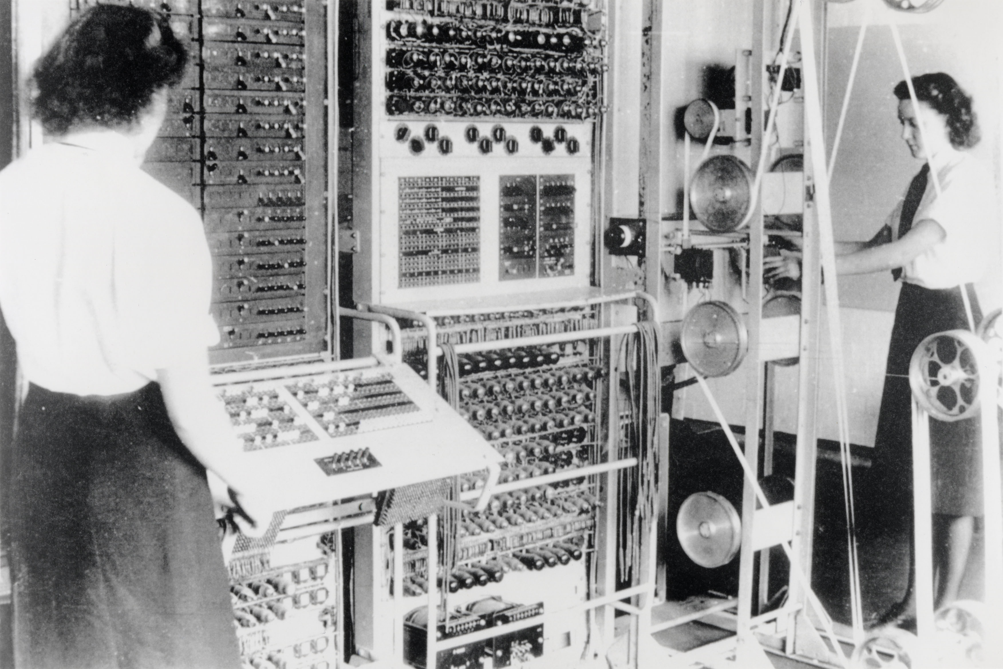 "A Colossus Mark 2 computer. The operator on the left is Dorothy Duboisson. The slanted control panel on the left was used to set the pin patterns on the Lorenz. The ""bedstead"" paper tape transport is on the right."