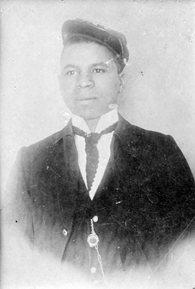 Head and torso of a young black man wearing a suit and tie with a watch chain hanging from a jacket button. He has a cap pushed high up on his forehead and tilted over his left ear.
