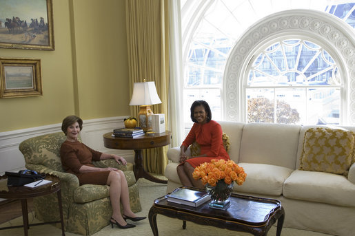 Another woman sits in a stuffed chair, and Michelle Obama sits on an adjacent couch.