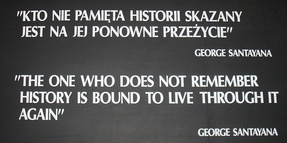 "A black placard with white text reading: ""KTO NIE PAMIẸTA HISTORII SKAZANY / JEST NA JEJ PONOWNE PRZEŻYCIE"" / GEORGE SANTAYANA / ""THE ONE WHO DOES NOT REMEMBER / HISTORY IS BOUND TO LIVE THROUGH IT / AGAIN"" / GEORGE SANTAYANA"