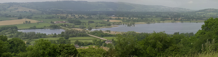photograph of the lake showing a road crossing via a causeway at Herriots Bridge. It is surrounded by green vegetation with hills in the distance