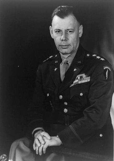 Three-quarter length portrait of seated man in uniform. He is bare-headed and wearing his medal ribbons. He is wearing the SHAEF shoulder sleeve insignia.